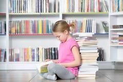 Милая книга чтения девушки в библиотеке Стоковая Фотография