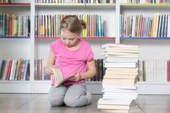 Милая книга чтения девушки в библиотеке Стоковые Фото