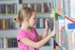 Милая книга чтения девушки в библиотеке Стоковая Фотография RF