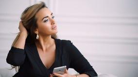 Милая коммерсантка в вскользь одеждах использует smartphone и усмехаться, сидя в стуле против современной белизны сток-видео