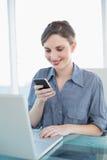 Милая коммерсантка используя ее smartphone сидя на ее столе Стоковое Изображение