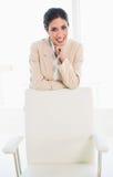 Милая коммерсантка стоя за ее стулом стоковое изображение rf