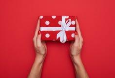 Милая конструированная подарочная коробка точки польки с белой лентой в руках f Стоковое Изображение RF
