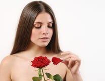 Милая красивая женщина срывает лепестки красной розы на белом backg Стоковые Фото