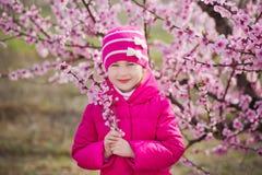 Милая красивая стильная одетая девушка брюнет при мама матери стоя на поле персикового дерева весны молодого с пинком стоковое фото