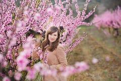 Милая красивая стильная одетая девушка брюнет при мама матери стоя на поле персикового дерева весны молодого с пинком стоковые изображения rf