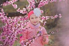 Милая красивая стильная одетая девушка брюнет при мама матери стоя на поле персикового дерева весны молодого с пинком стоковая фотография