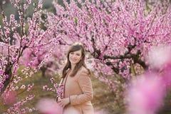 Милая красивая стильная одетая девушка брюнет при мама матери стоя на поле персикового дерева весны молодого с пинком стоковое изображение