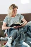 Милая кровать книги чтения девушки лежа мягко Стоковое Изображение