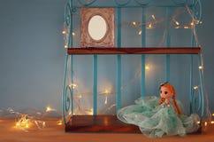 Милая кукла и пустая рамка фото рядом с теплой гирляндой освещают Стоковые Фото