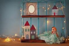 Милая кукла, пустая рамка фото и деревянные маленькие дома рядом с теплой гирляндой освещают Стоковая Фотография RF