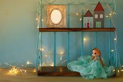 Милая кукла, пустая рамка фото и деревянные маленькие дома рядом с теплой гирляндой освещают Стоковая Фотография