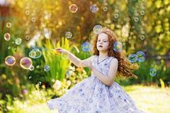 Милая курчавая девушка в платье летания играя с пузырями мыла Счастливый Стоковые Фотографии RF