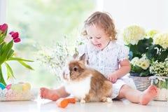 Милая курчавая девушка малыша играя с зайчиком Стоковая Фотография
