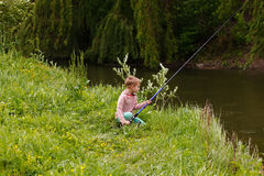 Милая малая рыбная ловля мальчика на реке Стоковая Фотография