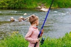 Милая малая рыбная ловля мальчика на реке Стоковые Фото