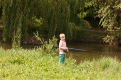Милая малая рыбная ловля мальчика на реке Стоковое фото RF