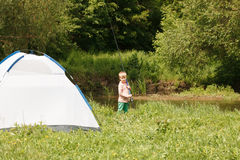 Милая малая рыбная ловля мальчика на реке Стоковое Фото