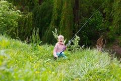 Милая малая рыбная ловля мальчика на реке Стоковые Изображения RF