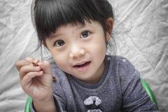 Милая маленькая азиатская девушка держа карандаш в руке Стоковые Фотографии RF