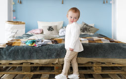 Милая маленькая белокурая девушка в спальне Портрет симпатичной маленькой белокурой девушки в спальне Стоковые Фотографии RF