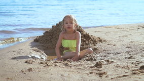 Милая маленькая белокурая девушка играя с песком на озере видеоматериал