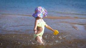 Милая маленькая белокурая девушка имея потеху озером акции видеоматериалы