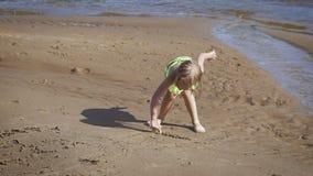 Милая маленькая белокурая девушка имея потеху озером видеоматериал