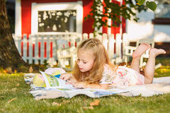 Милая маленькая белокурая книга чтения девушки снаружи на траве Стоковые Изображения