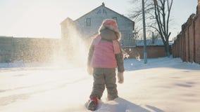 Милая маленькая девочка бежать в снеге, имеющ потеху сток-видео