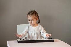 Милая маленькая девочка в белой рубашке играя электронный рояль Стоковые Фотографии RF