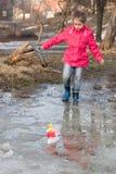 Милая маленькая девочка в ботинках дождя играя с красочной заводью кораблей весной идя в воду стоковое изображение