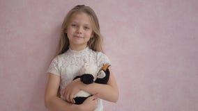 Милая маленькая девочка в вскользь одеждах держа мягкую игрушку и усмехаясь на камере сток-видео