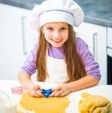 Милая маленькая девочка в кухне подготавливая печенья Стоковые Фото