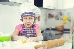 Милая маленькая девочка в печеньях выпечки рисбермы дома стоковая фотография