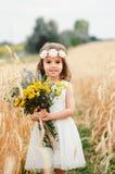 Милая маленькая девочка в поле лета пшеницы Ребенок с букетом wildflowers в его руках Стоковое Фото
