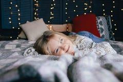Милая маленькая девочка в свитере на кровати Стоковые Фотографии RF