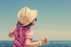 Милая маленькая девочка в соломенной шляпе на пляже Стоковое Фото