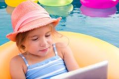 Милая маленькая девочка в шляпе используя компьтер-книжку пока в бассейне Стоковые Изображения RF