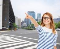 Милая маленькая девочка в eyeglasses указывая в воздух Стоковое фото RF