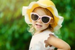 Милая маленькая девочка в striped платье и шляпе ослабляя на пляже около моря, лета, каникул, концепции перемещения усмехаться стоковые фотографии rf