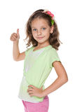 Милая маленькая девочка держит ее большой палец руки вверх Стоковые Фотографии RF