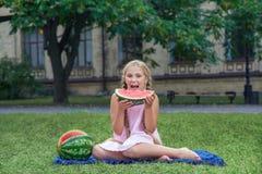 Милая маленькая девочка есть арбуз на траве в временени при волосы ponytail длинные и зубастая улыбка сидя на траве и enjo Стоковые Фото