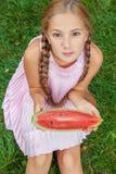 Милая маленькая девочка есть арбуз на траве в временени при волосы ponytail длинные и зубастая улыбка сидя на траве и enjo Стоковые Изображения RF