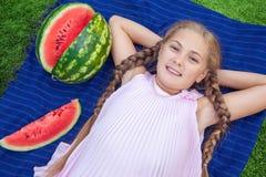 Милая маленькая девочка есть арбуз на траве в временени при волосы ponytail длинные и зубастая улыбка сидя на траве и enjo Стоковое Изображение RF
