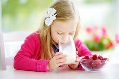 Милая маленькая девочка есть поленики и питьевое молоко дома Милый ребенок наслаждаясь ее здоровыми свежими фруктами и ягодами стоковые фото