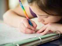 Девушка делая ее домашнюю работу Стоковые Фото