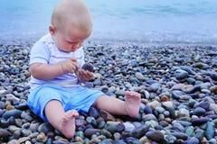 Милая маленькая девочка играет с ведром на пляже, собирая утесы Стоковые Фотографии RF