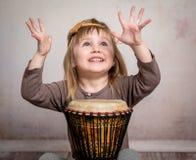 Милая маленькая девочка играя барабанчик Стоковые Изображения