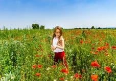 Милая маленькая девочка играя в красных маках field летний день, красота Стоковая Фотография RF